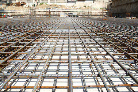 monolith: workers in the construction site making reinforcement metal framework for concrete pouring