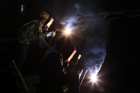 skilled labour: In the steel mill workshop, welding workers are working