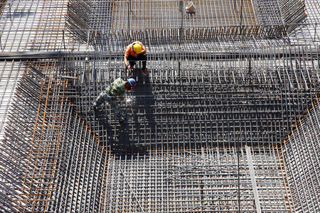 concrete construction: worker in the construction site making reinforcement metal framework for concrete pouring Stock Photo