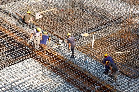 materiales de construccion: trabajador en la estructura met�lica de refuerzo toma de emplazamiento de la obra de hormigonado Editorial