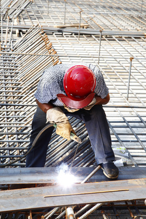 reinforcement: The welding worker in the construction site making reinforcement metal framework for concrete pouring Stock Photo