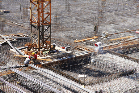 site construction: worker in the construction site making reinforcement metal framework for concrete pouring Stock Photo