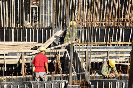 on site: builder worker knitting metal rods bars into framework reinforcement for concrete pouring at construction site Editorial