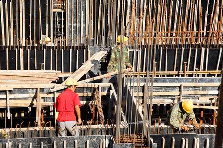 materiales de construccion: constructor varillas de tejer trabajador del metal en barras de refuerzo marco para el vertido del hormig�n en obra de construcci�n Editorial