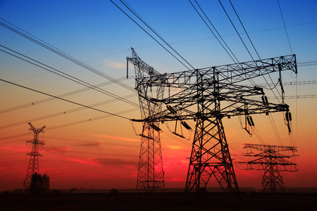isolator high voltage: The silhouette of the evening electricity transmission pylon