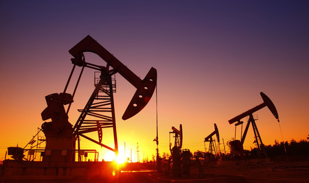 mechanical works: Oil field scene, the evening of beam pumping unit in silhouette Stock Photo
