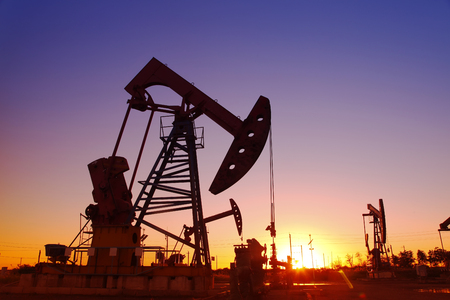 torres petroleras: escena del campo petrol�fero, la tarde del grupo de bombeo viga en silueta Foto de archivo