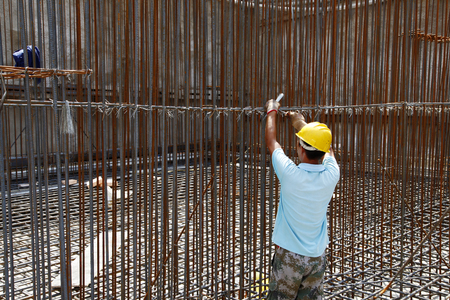 reinforcement: worker in the construction site making reinforcement metal framework for concrete pouring Stock Photo