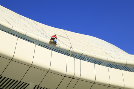 steeplejack: Workers cleaning the roof of a modern office building