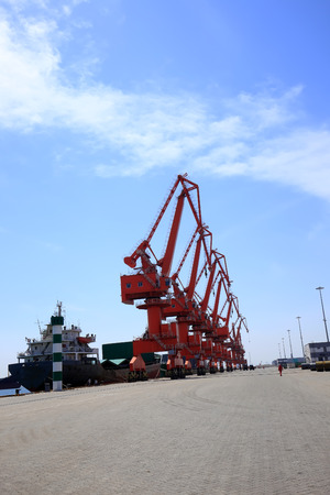 gantry: In freight terminal, gantry crane and cargo ships are in loading and unloading of goods Stock Photo