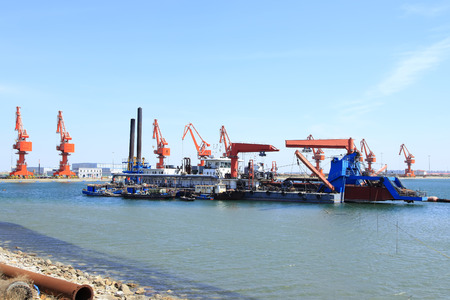 unloading: In freight terminal, gantry crane and cargo ships are in loading and unloading of goods Stock Photo