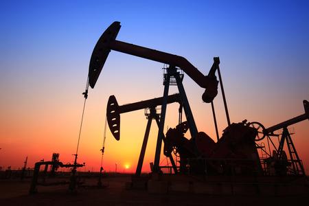 natural resources: La tarde del campo petrolífero, la unidad de bombeo y la silueta de la torre de perforación de yacimientos petrolíferos Foto de archivo