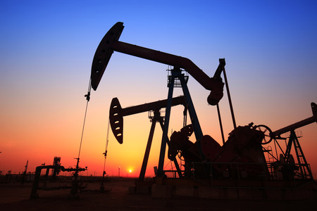 natural resources: The evening of the oilfield, pumping unit and the silhouette of oilfield derrick Stock Photo