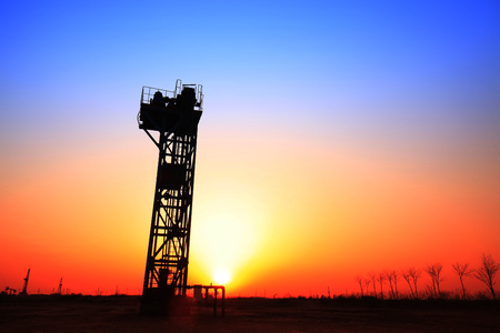 mechanical works: In the evening, the silhouette of the oil pump Stock Photo