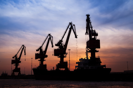 commerce and industry: In the evening, the silhouette of port cranes
