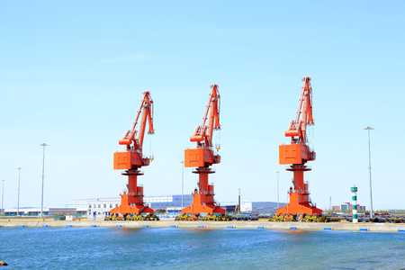 gantry: In freight terminal, gantry crane and cargo ships are in loading and unloading of goods Editorial