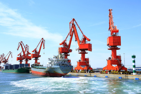 In freight terminal, gantry crane and cargo ships are in loading and unloading of goods Stock Photo
