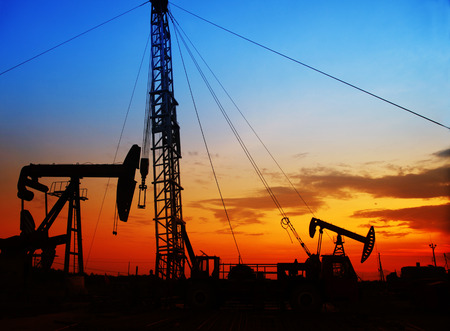 The evening of the oilfield, pumping unit and the silhouette of oilfield derrick Stock Photo