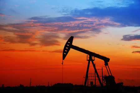 Oil field scene, the evening of beam pumping unit in silhouette Stock Photo