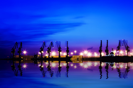 Cargo port in the evening, silhouette of gantry crane
