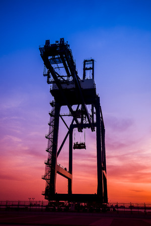Cargo port in the evening The silhouette of gantry crane