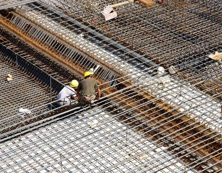 Travailleur sur le chantier de construction faisant l'armature métallique de renfort pour le coulage du béton
