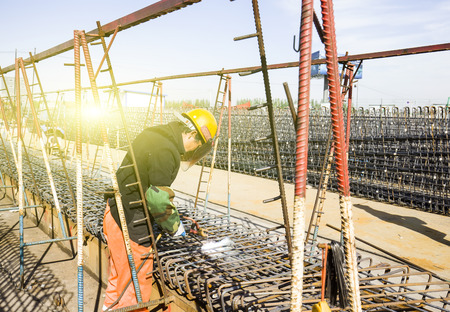 Welding workers at work in the construction area Editorial