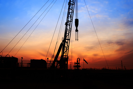 Landscape view of the oilfield derrick during sunset Stock Photo
