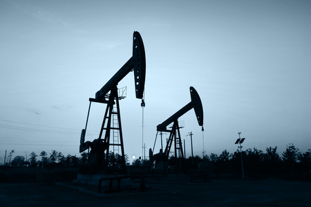 The silhouette of the oil pump in the evening Stock Photo
