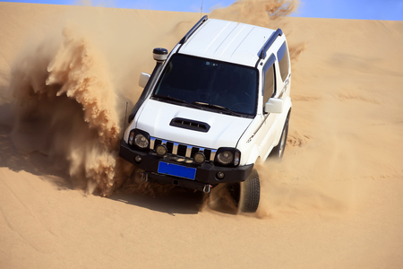 An suv was driving in the desert.