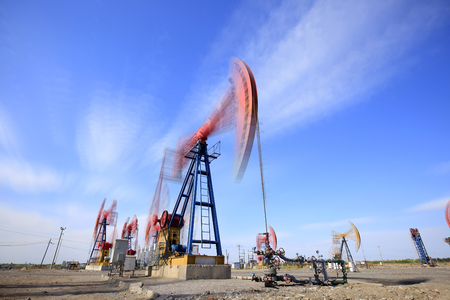 At the oil field, the oil pump is running, blue sky and white clouds