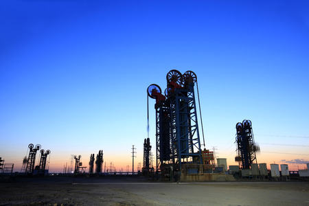 Oil field, the tower type pumping unit in the evening Stock Photo