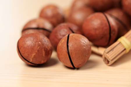 Macadamia nuts on a wooden background