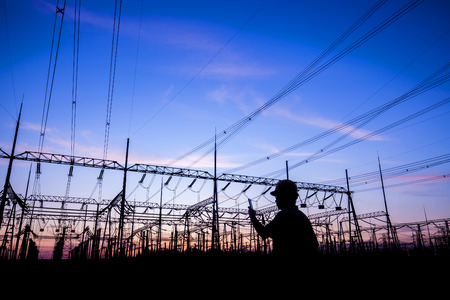 Power workers at work, silhouettes of power towers Standard-Bild