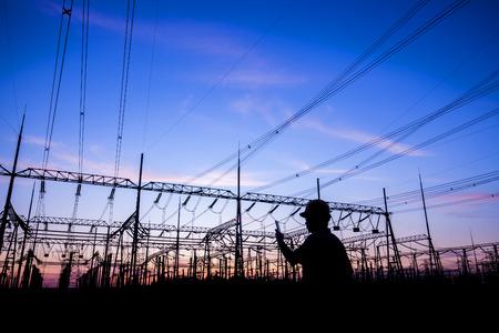 Travailleurs de l'électricité au travail, silhouettes de tours électriques Banque d'images