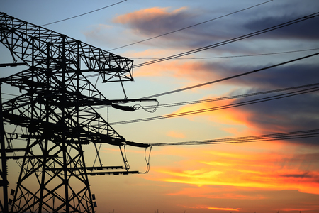 In the evening, high voltage towers silhouette and a beautiful sunset Imagens