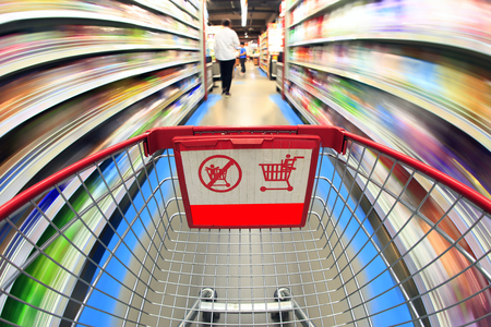 Empty shopping cart in the supermarket, background blurred