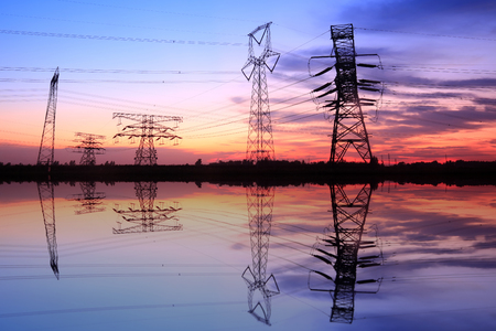 Silhouette of high voltage towers and sunset scenery Stock Photo