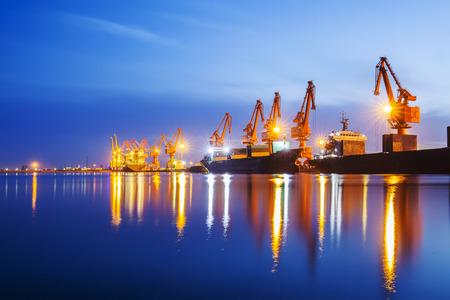 Grue à portique et cargo le soir, concept d'expédition et de logistique
