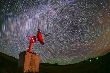 In observatories,satellite antenna radio telescope on the background of stellar tracks 写真素材