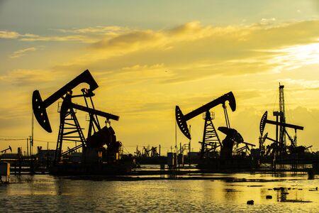 Sitio del campo petrolífero, por la noche, las bombas de aceite están funcionando