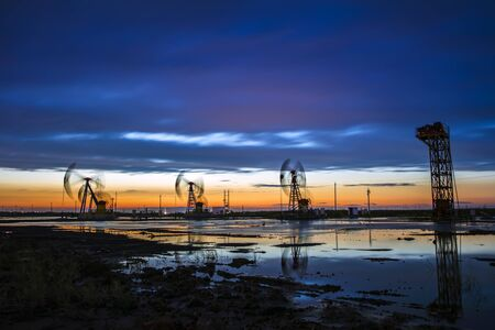 Oil field site, in the evening, oil pumps are running Stockfoto