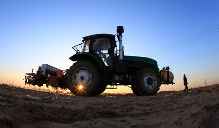 In the spring,The tractor in farmland farming