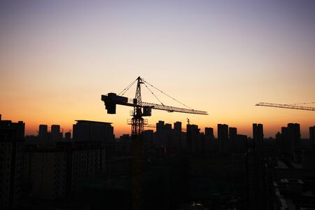 Le gru a torre costruiscono edifici residenziali di notte Archivio Fotografico