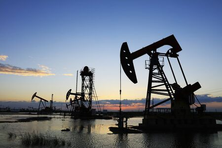 Oil field site, in the evening, oil pumps are running Stock Photo