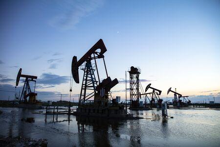 Oil field site, in the evening, oil pumps are running Foto de archivo