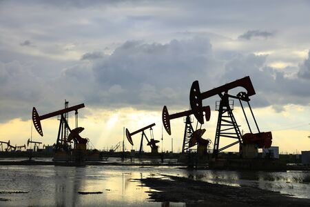 Oil field site, in the evening, oil pumps are running Banque d'images