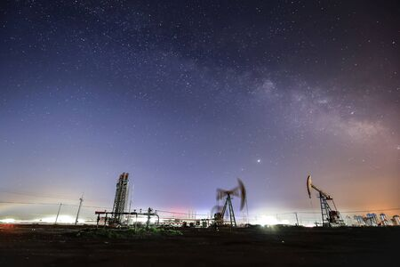 At night, oil pumps under the stars
