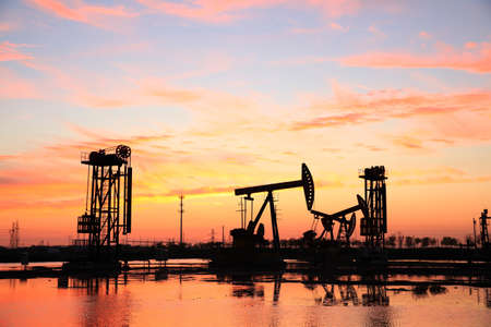 Oil field site, in the evening, oil pumps are running, The oil pump and the beautiful sunset reflected in the water, the silhouette of the beam pumping unit in the evening. Stock Photo