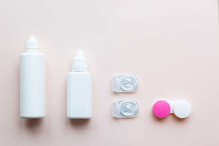 Contact lenses, lens solution and lens containers on a light pink background. Health care concept top view copy space 版權商用圖片